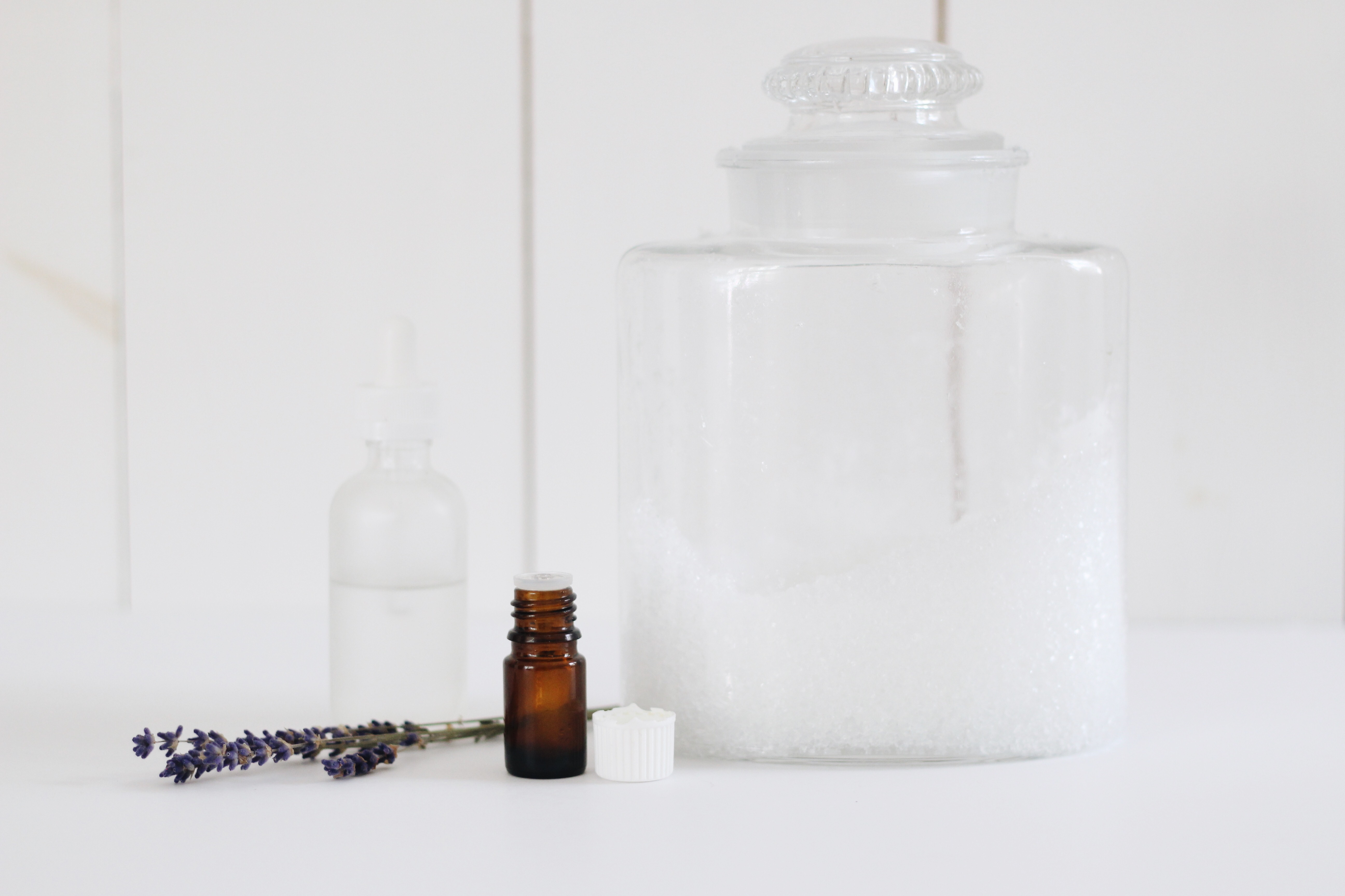 epsom salts in a glass jar, with an amber bottle of essential oil