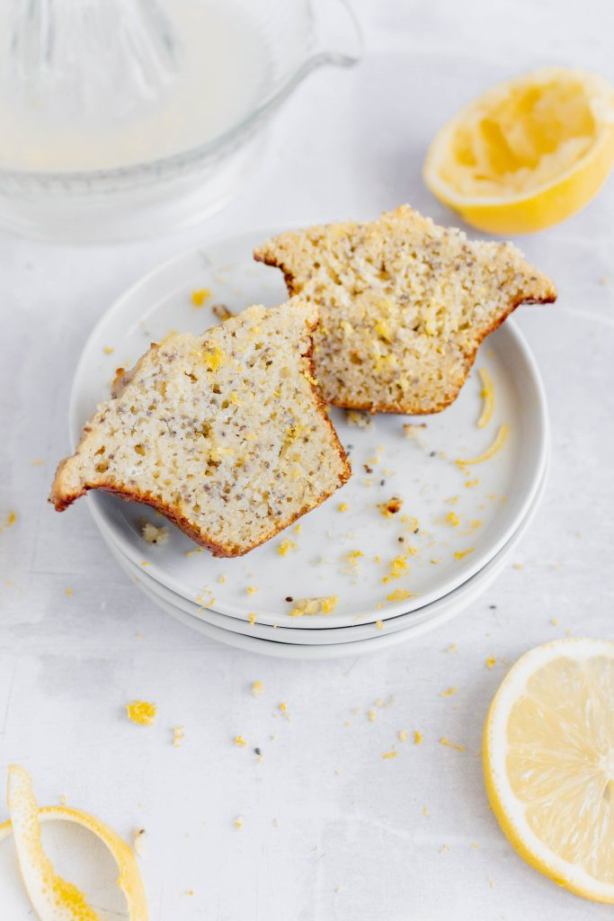 Healthy Lemon Chia Seed Muffin sliced in half on a plate, with lemon slices and lemon zest.