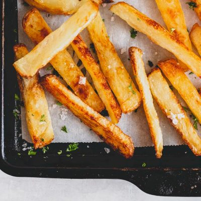 oven baked french fries on baking sheet from above, on grey surface with blue and white tea towel