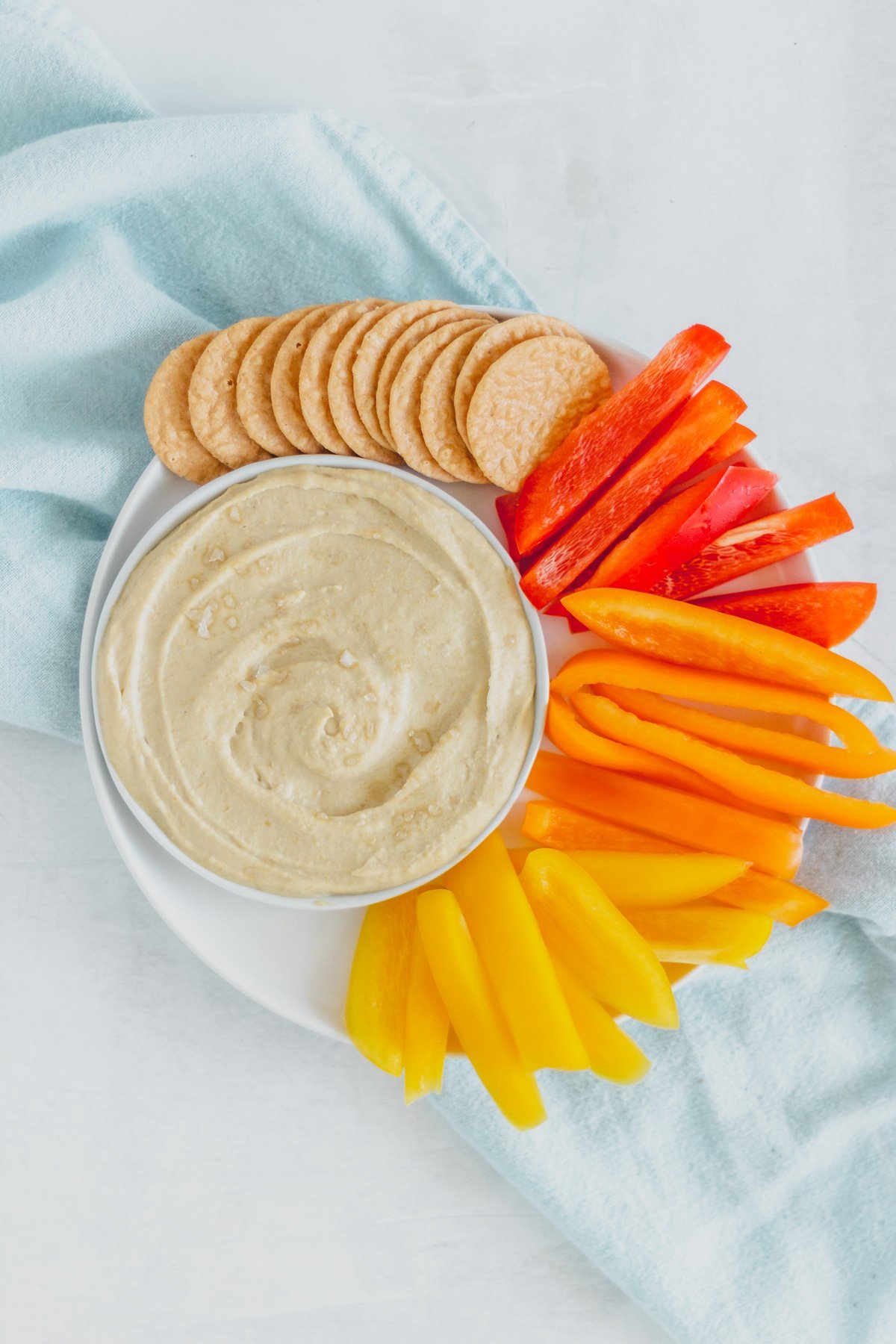 Overhead view of hummus on white plate with crackers and sliced bell peppers, with light blue tea towel