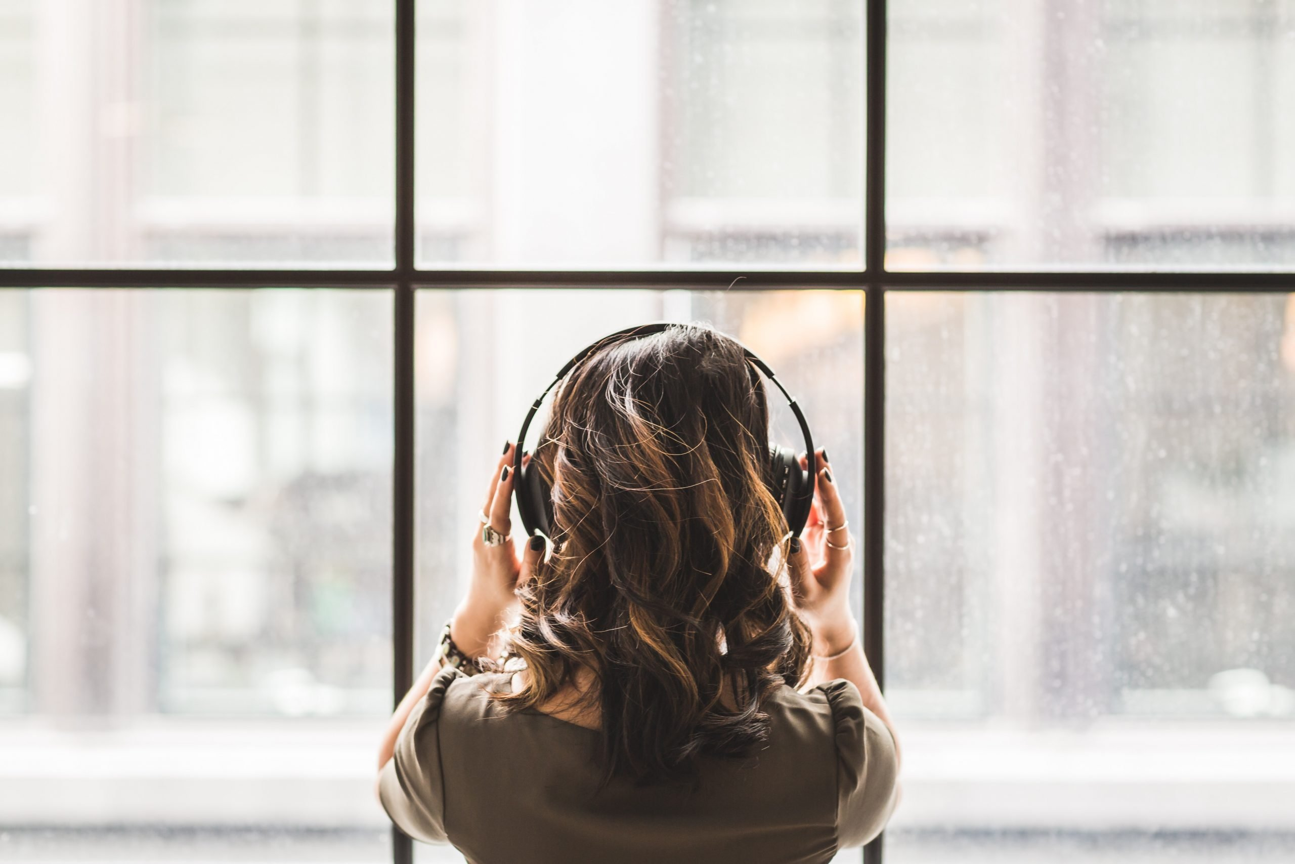 woman with headphones, looking out window