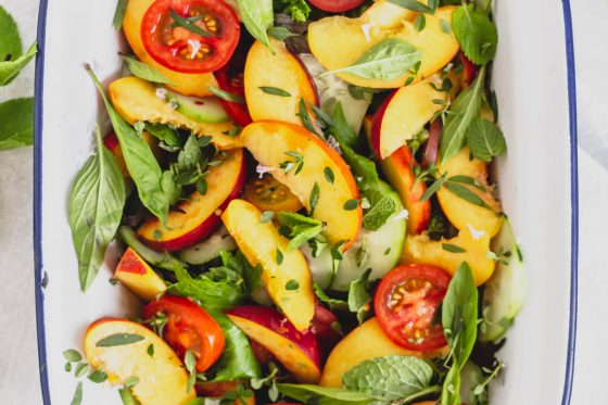 overhead view of peach cucumber salad with herbs in white enamel bowl with blue rim, on grey surface with tea towel and herbs