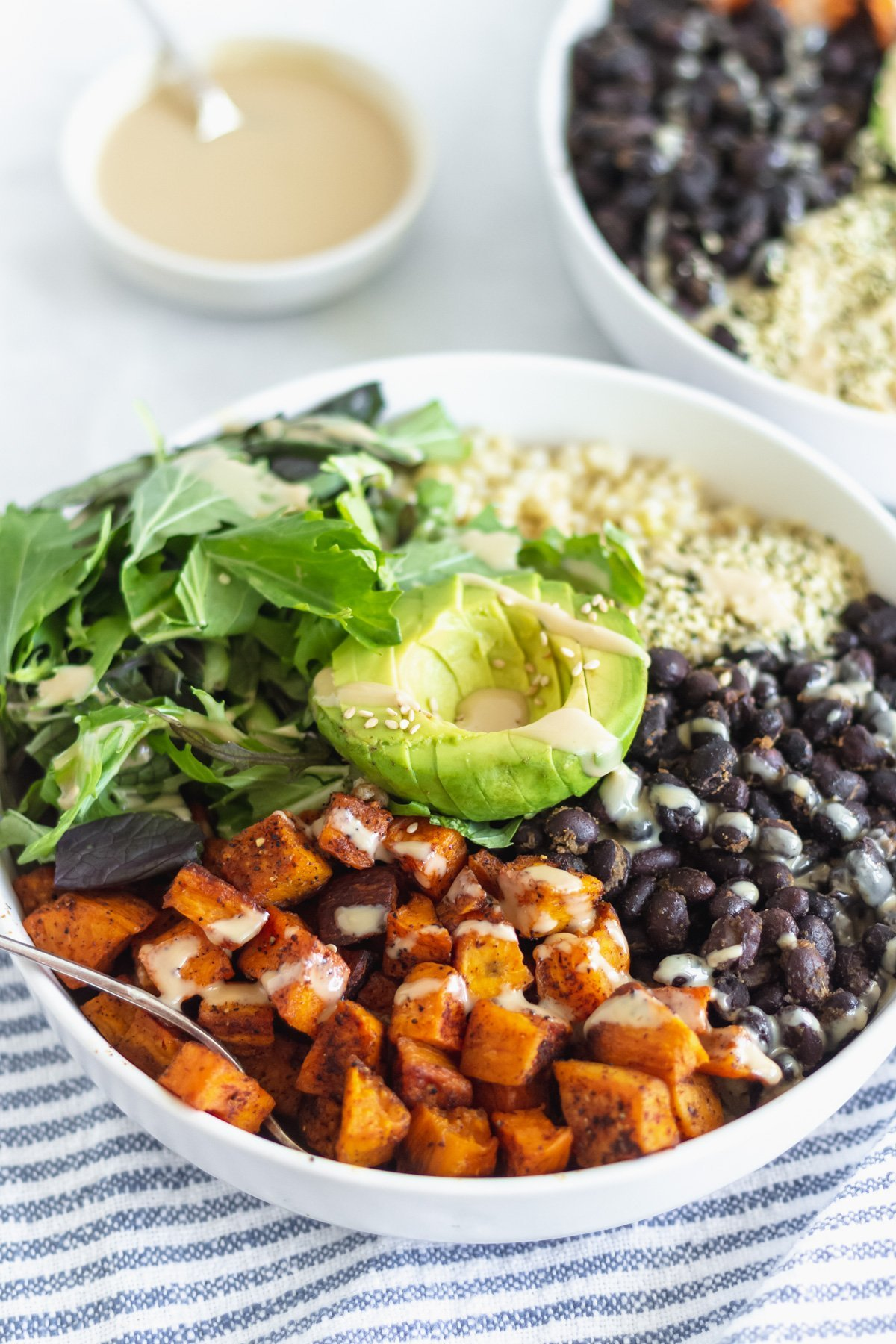 sweet potato, black beans, brown rice, leafy greens, and avocado in a buddha bowl drizzled with tahini dressing