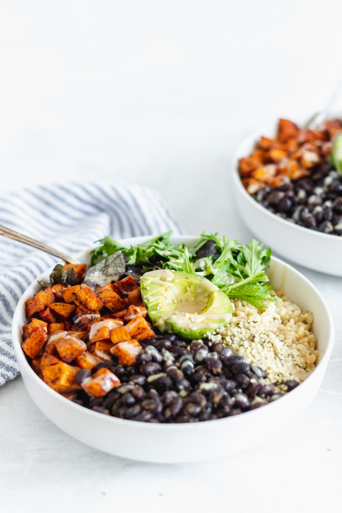 sweet potato, black beans, brown rice, leafy greens, and avocado in a buddha bowl with from 45º angle