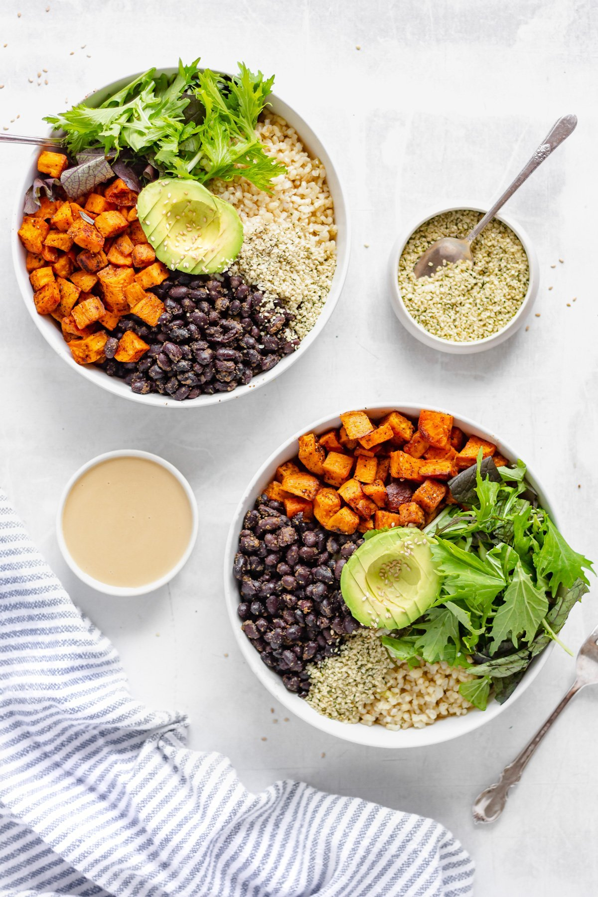 two white bowls containing: sweet potato, black beans, brown rice, leafy greens, and avocado from overhead. Two separate ramekins contain tahini dressing and hemp seeds.
