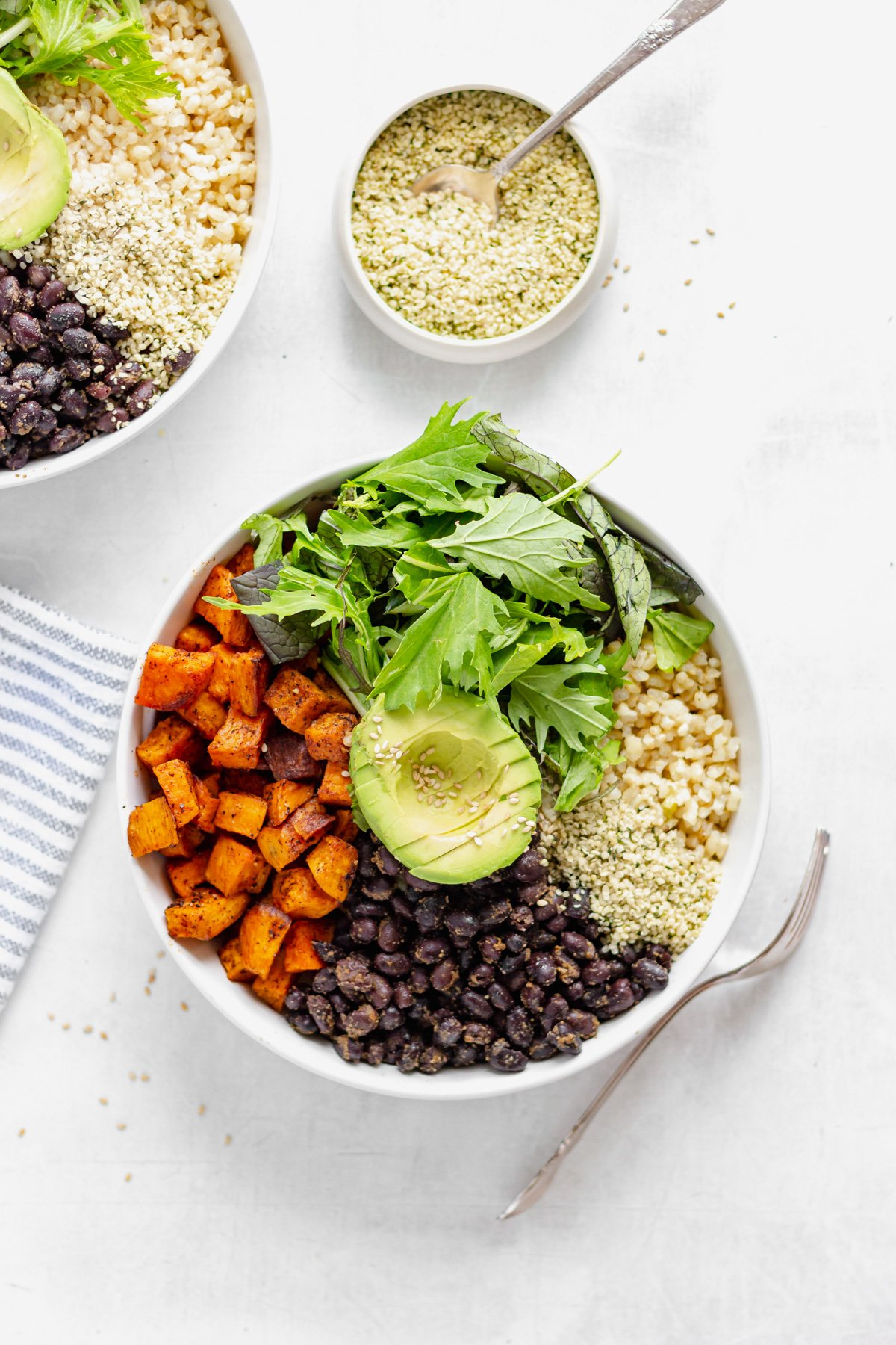 sweet potato, black beans, brown rice, leafy greens, and avocado in a buddha bowl with hemp seeds on the side, from overhead