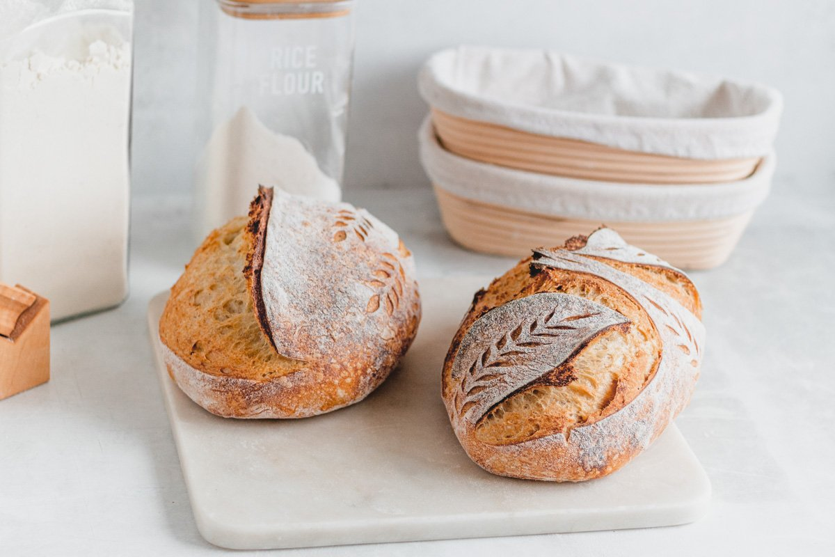 two loaves of sourdough bread on white backdrop with sourdough bannetons in background