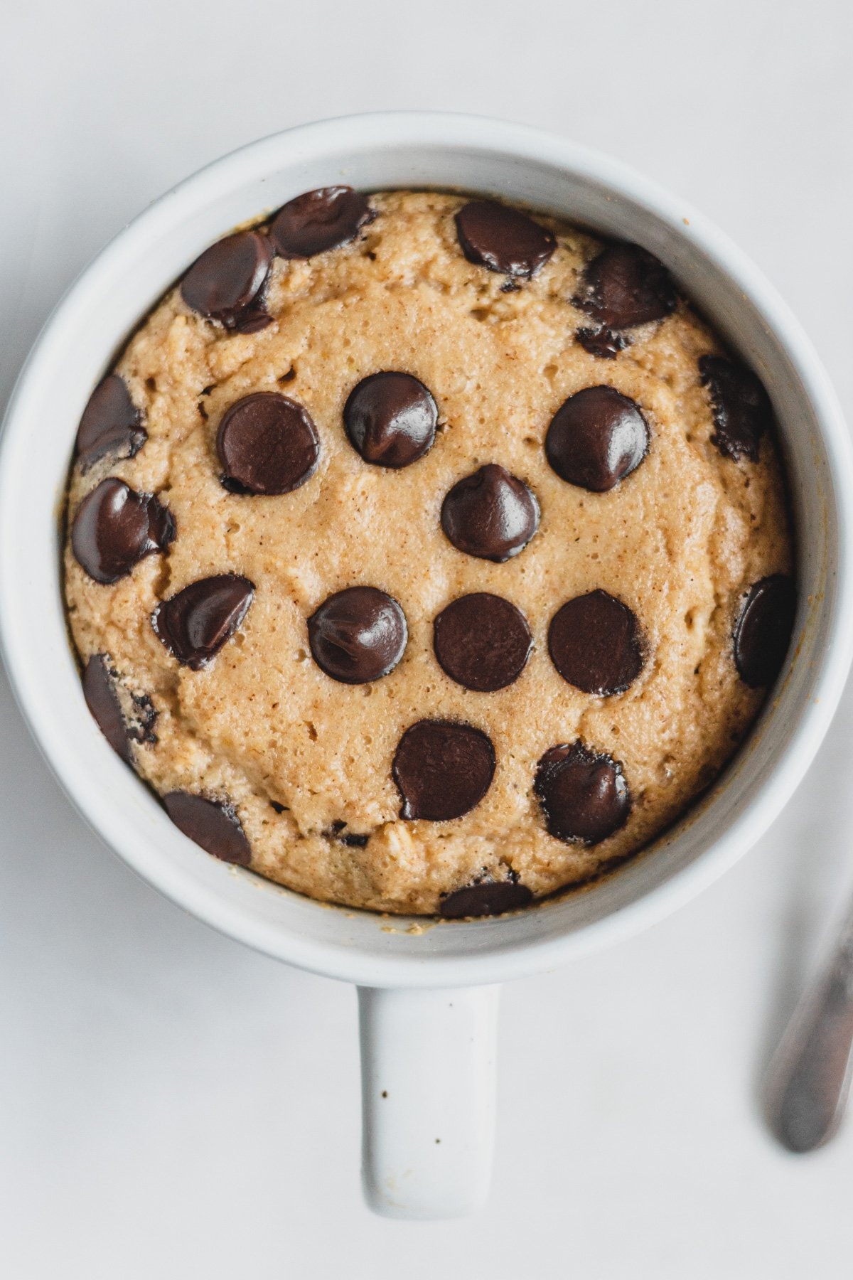 single serve baked oatmeal in a mug, from overhead view. Top is covered in chocolate chips.