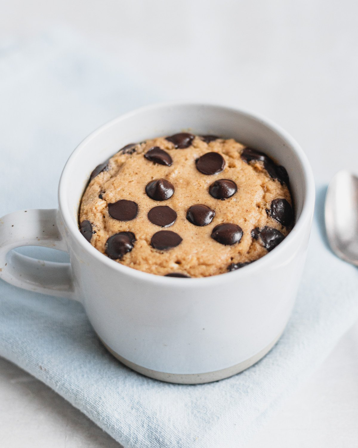 single serve cookie dough baked oatmeal in a white mug, on light grey backdrop with spoon and blue linen napkin