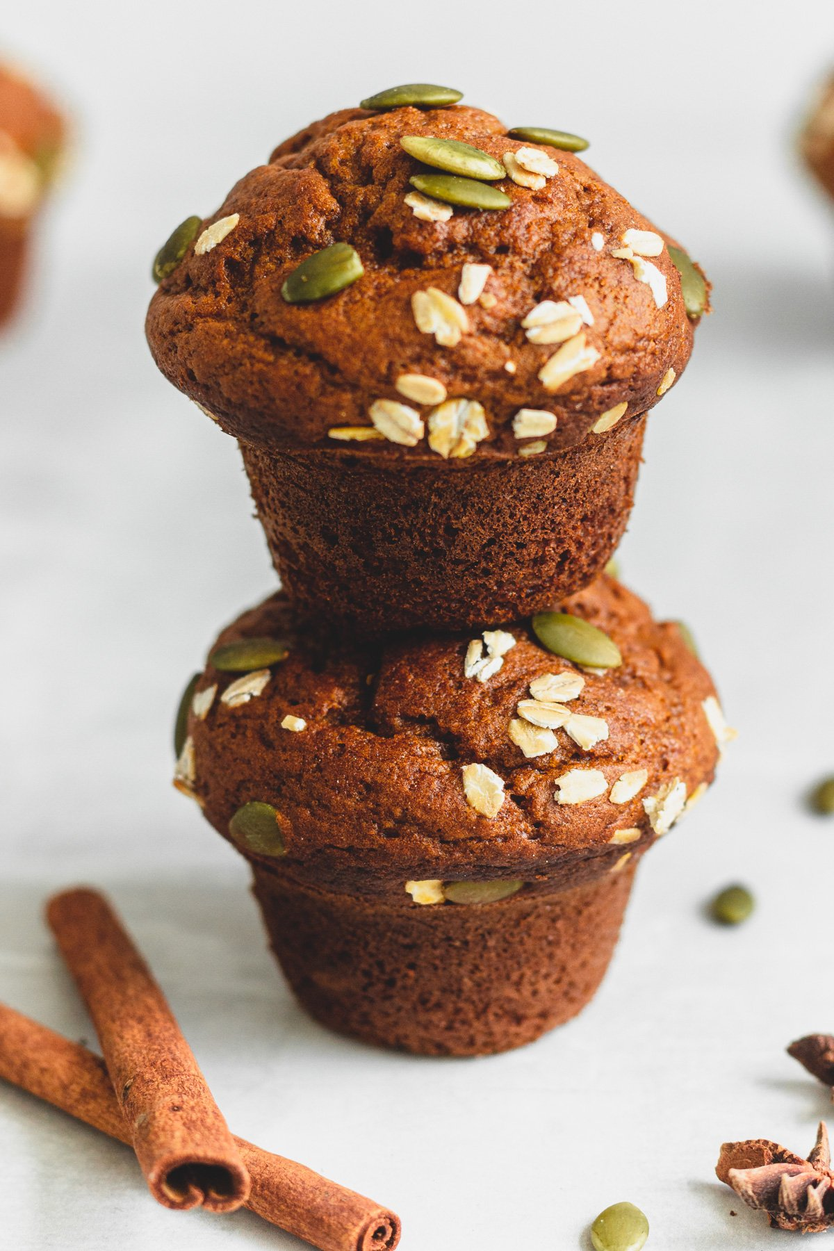 two pumpkin muffins, one stacked on top of the other from a 90º angle, on grey surface with cinnamon sticks, pumpkin seeds and anise