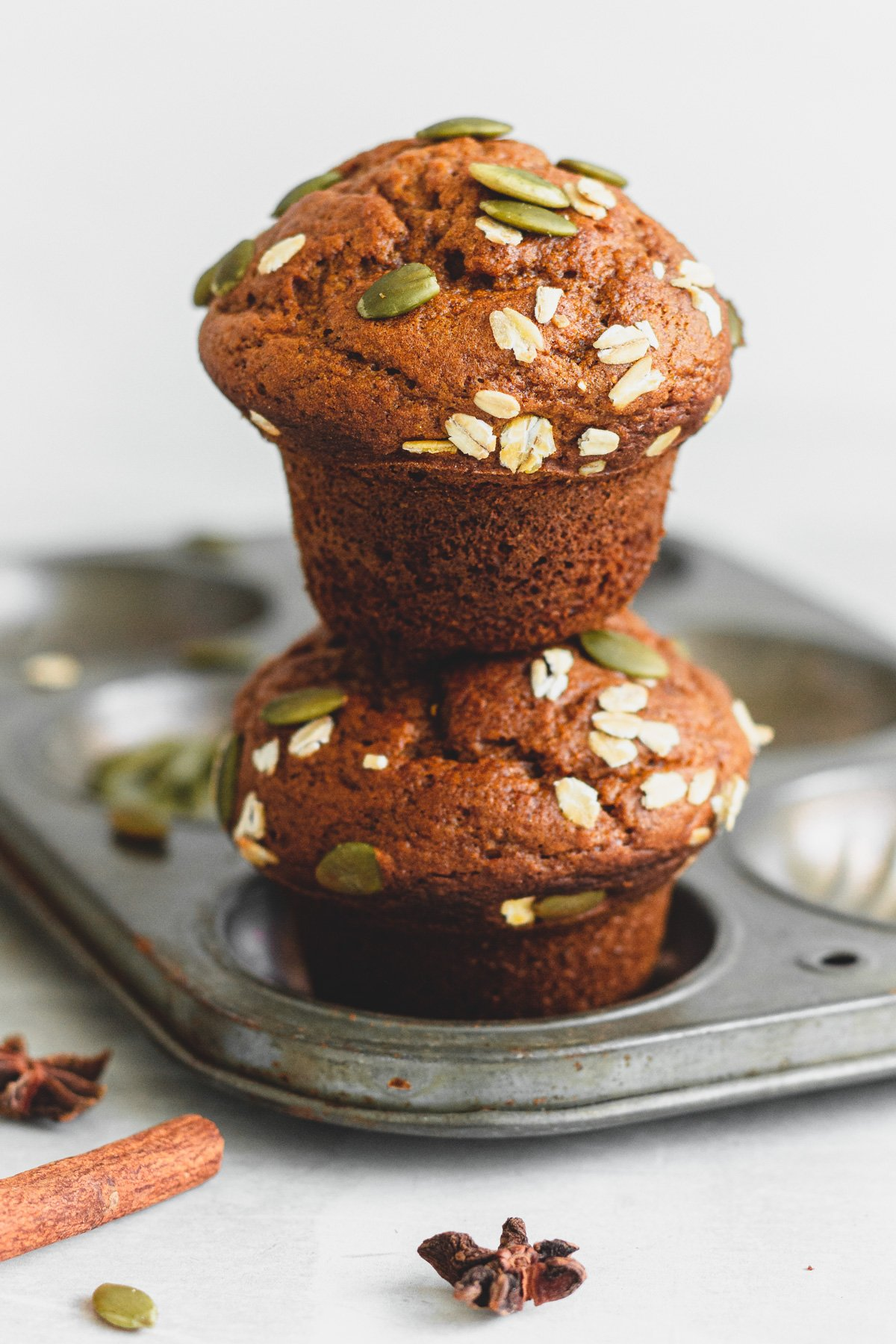 two pumpkin muffins, one stacked on top of the other from a 90º angle, on muffin tin with cinnamon sticks, pumpkin seeds and anise