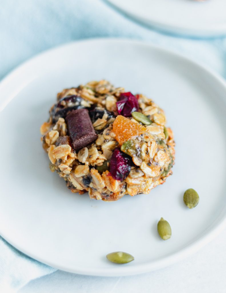 cranberry almond breakfast cookie on a white plate, with light blue napkin in background