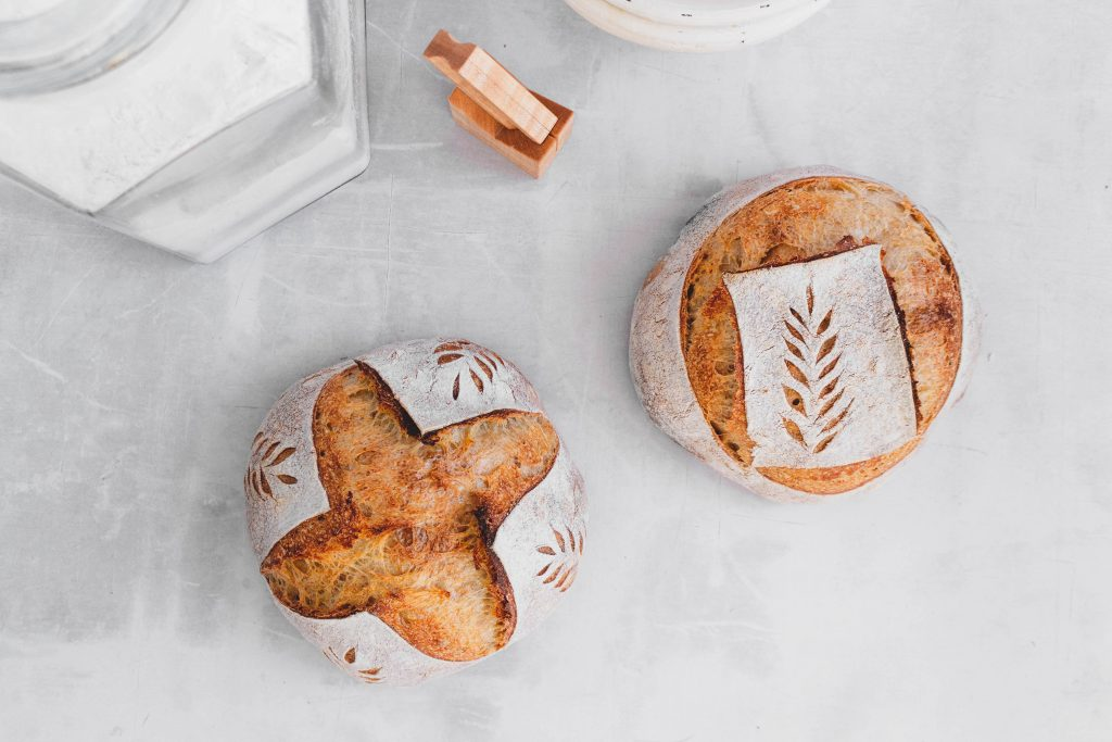 two loaves of sourdough bread on white backdrop